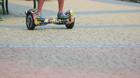 мини : 17.09.2017 - Kyiv, Ukraine. Driving gyroscooter on cobblestone surface. Close up, front view. Colourful trendy gadget.