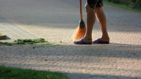 süpürge : Sweeping cut grass from cobblestone pavement. Public janitor cleaning park street. Stok Video