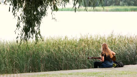 kamış : Woman playing a guitar by the banks of the river. Back view. Wind blow, reeds on river.