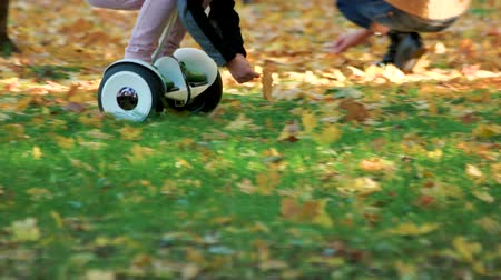 gyroscope : Riding electrical gyro scooter on the grass. Girl picking up golden leaves.