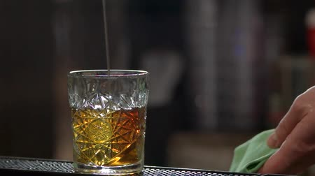 замораживать : Pouring rum, slow motion. Glass of alcohol drink, close up.