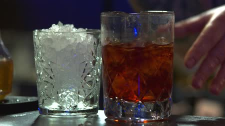 パブ : Stirring brandy with ice, close up. Barman making brandy coctail with ice.