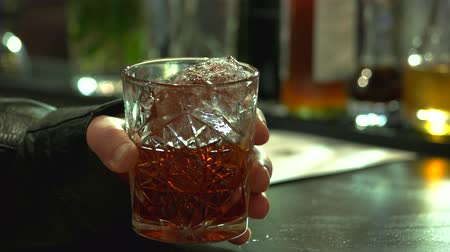 eklemek : Close up male hand holding glass of brandy with ice. Brown whiskey with piece of ice. Drinking in a bar. Stok Video