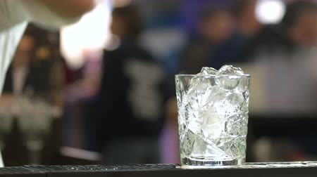 şarap kadehi : Barman cooking cocktail on bar counter. Glass of ice cubes, close up. Stok Video