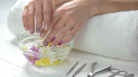 chrysanthemum : Spa treatment for female hands. Young woman beautiful hands in glass bowl with water and floating chrysanthemums. Hands treatment and nails care.
