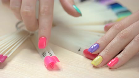 основа : Manicured hand choosing nail polish. Artificial nails on transparent basis. Varnish color palette for nails. Woman in nail salon. Стоковые видеозаписи