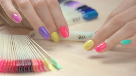 основа : Nail polish samples in female hands. Nail polish testers and young woman manicured hands. Girl choosing perfect nail varnish color.
