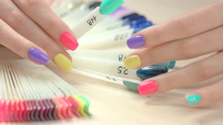 unha : Set of multicolored nail in female hands. Woman manicured hand choosing color of nail polish in professional nail studio.