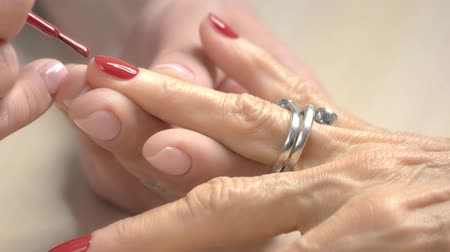professionally : Manicurist professionally applying varnish on nails. The process of accurately painting nails to old woman with red polish in nail studio close up. Stock Footage
