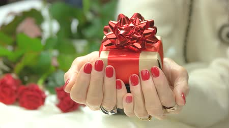 unha : Gift box in female manicured hands. Senior woman hands with red manicure holding red gift box with bow. Holidays and celebrations concept.