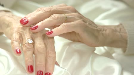 bölcs : Well-groomed hands with jewelry. Caucasian senior woman hands with red manicure wearing expensive rings. Stock mozgókép