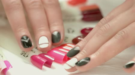 zománc : Manicured fingers and nails color samples. Girl hands with stylish matte manicure choosing nail color in beauty salon close up. Stock mozgókép
