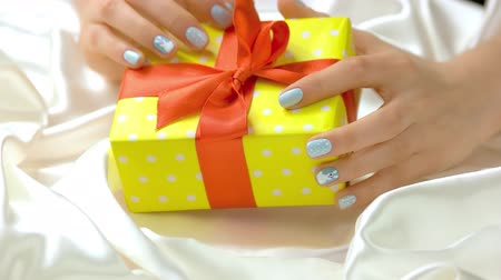 womanhood : Beautiful gift and female hands. Young woman manicured hands and yellow gift box on white silk. New Year and Christmas concept. Stock Footage