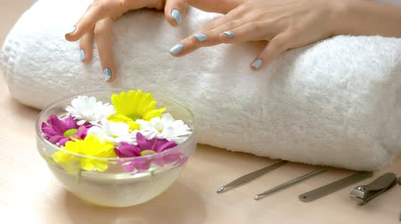chryzantema : Female hands receiving spa treatment. Female manicured hands on towel. Womans hands with winter manicure is getting spa procedure. Hands and nails spa treatment.