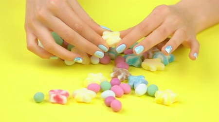 dokonalost : Manicured hands and colored candies. Woman hands with beautiful winter manicure placing multicolored sweet candies on yellow background. Dostupné videozáznamy