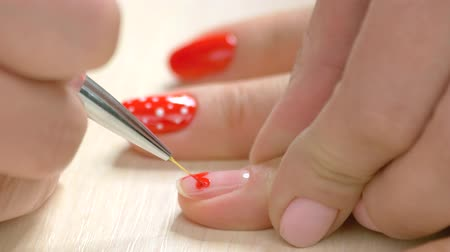 professionalism : Heart drawing on nails by beautician. Beauty salon manicure session, woman hand painting heart pattern on female nail close up. Stock Footage