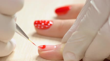 professionalism : Close up manicurist painting on nails. Beauty salon manicure session, woman hand painting pattern of heart on female nail close up.