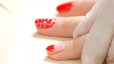 professionalism : Cosmetician painting a pattern on female nail. Nail beautician drawing white dots on ring finger nail. Nail art studio.