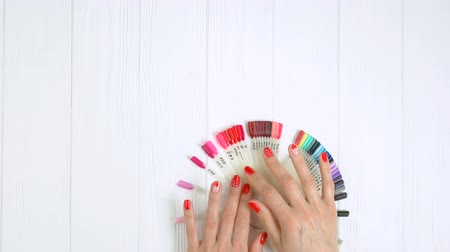 desenli : Red manicure and nail color samples. Woman hands choosing nail color. Nail color palette on white wooden table, top view.