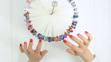 turn table : Big variety of nail art samples, manicured hands. Woman hands choosing nail design on nail art palette, top view. Woman in nail salon. Stock Footage