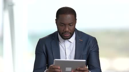 dark skinned : Funny african-american businesssman playing computer game. Handsome dark-skinned man in business suit playing online game on pc tablet.