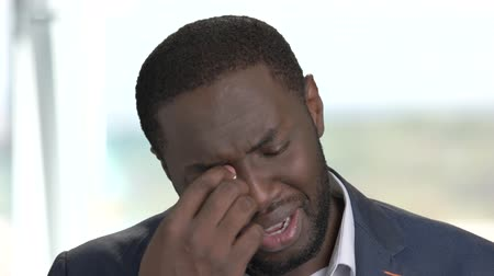 dark skinned : Close up afro-american businessman is crying. Dark-skinned man in formal wear crying and wiping tears on blurred background. Human expressions of sorrow.