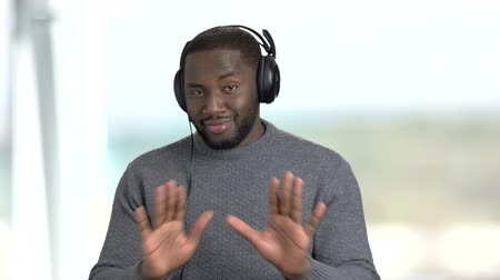 darkskinned : Afro-American guy in headphones is dancing. Handsome african-american man listening music in headphones and dancing on blurred background.