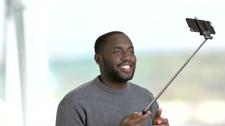 dark skinned : Funny dark-skinnesd guy using monopod. Cheerful man making face grimace while taking selfie with selfie stick on blurred background.
