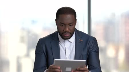 dark skinned : Funny dark-skinned businessman playing online game. Afro-american man in business suit playing game on pc tablet. Break at work.