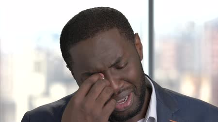 dark skinned : Face of crying afro-american man. Desperate dark-skinned businessman on blurred background. Despair man regrets about something. Stock Footage