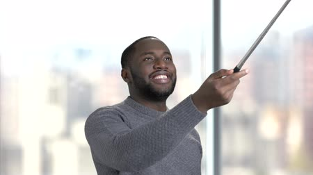 telescopic : Smiling man with selfie stick on blurred background. Handsome afro-american guy using monopod indoor. People and modern technology.