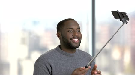 dark skinned : Young black man using selfie stick. Cheerful afro-american guy having fun while taking selfie of himself with monopod on blurred background. Stock Footage