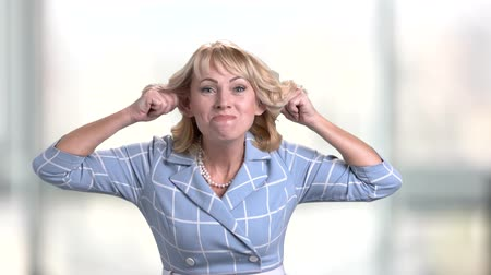 ожерелье : Mature woman making grimace. Middle-aged woman making funny face on blurred background. Emotions and facial expressions concept.