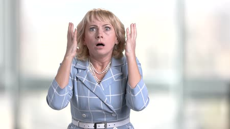 chocado : Horrified mature woman on blurred background. Caucasian middle-aged woman looking frightened and stressed holding hands on head. Human negative expressions.