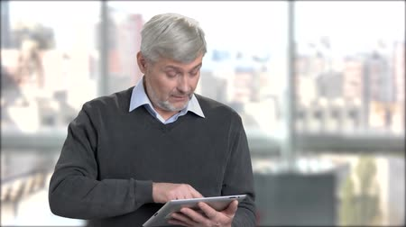 přenosný : Mature man typing message on digital tablet. Friendly senior man using pc tablet on office window background. Senior people and modern technology.
