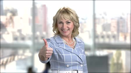 taça : Cheerful business woman gesturing thumbs up. Happy smiling female person giving two thumbs up on window city background. Symbol of success.