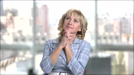 clasped : Smiling mature blonde with clasped hands. Pretty romantic woman is dreaming on window city background. Portrait of woman fell in love. Stock Footage