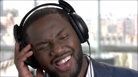 dark skinned : Close up smiling face of businessman in headphones. Cheerful african-american man listening to music in headphones close up.