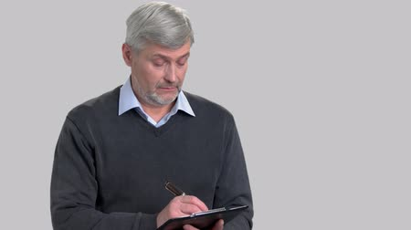 audit : Confident mature man writing on clipboard. Caucasian supervisor making a note on clipboard on grey background. People and occupation concept.