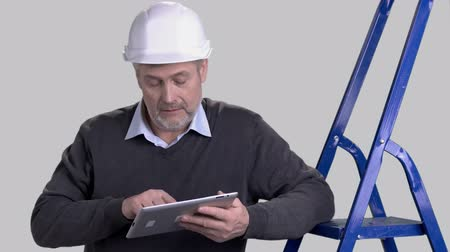 hard hat : Mature architect using computer tablet. Confident engineer in hard hat working on pc tablet on grey background.