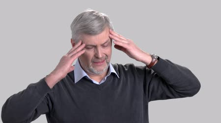 dor de cabeça : Mature caucasian man suffering from headache. Stressed man rubbing his temples because of strong headache on grey background. Portrait of overworked man with migraine. Stock Footage