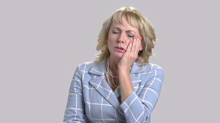 dor de dente : Mature blonde suffers from tooth pain. Stressed woman touching her cheek because of strong toothache on gray background. Dental problem concept.