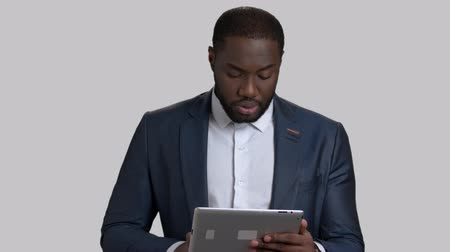 dark skinned : Confident businessman speaking on grey background. Handsome afro-american man in formal wear using computer tablet and talking. Manager talking at conference.
