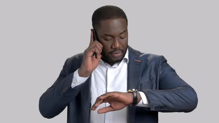 punctuality : Businessman using phone and looking on wristwatch. Confident afro-american businessman talking on mobile phone and checking his wristwatch on grey background.