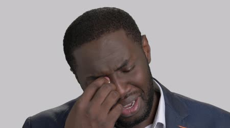 regretting : Crying black businessman in full despair. Face of unhappy desperate afro-american businessman is wiping tears on grey background close up. Stress and sorrow.
