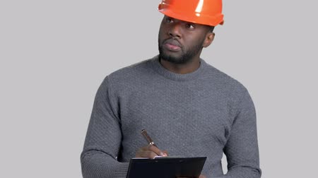 dark skinned : Afro-american supervisor writing on clipboard. Handsome dark-skinned engineer making a note on clipboard on grey background. Stock Footage