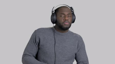 darkskinned : Handsome man in headphones is dancing. Attractive dark-skinned guy is listening to music in headphones and dancing on grey background.