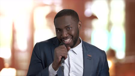 dark skinned : Joyful man is singing in microphone. Young happy Afro-American guy is singing with microphone and looking at camera on blurred background. Stock Footage