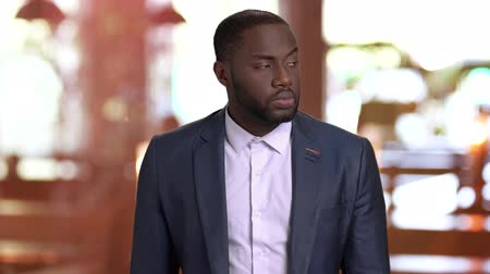 punctuality : Portrait of businessman is waiting for someone. Afro-american businessman is looking around on blurred background. Businessman is waiting for his girlfriend. Stock Footage