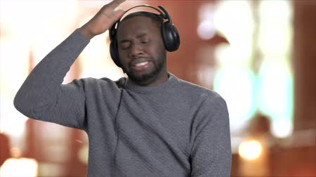 darkskinned : Energetic man listening to music in headphones. Handsome afro-american guy in headphones dancing and giving thumbs up on blurred background. Stock Footage
